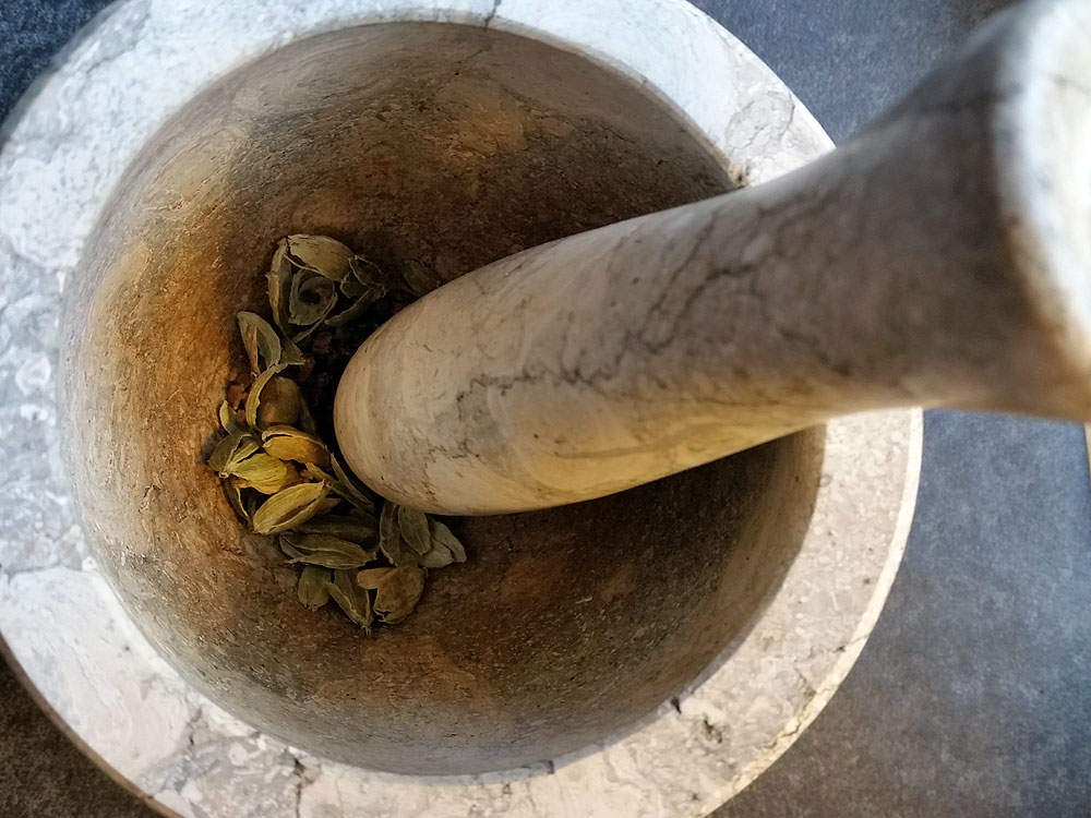 I grind the ingredients (here cardamom pods) with a mortar and pestle.