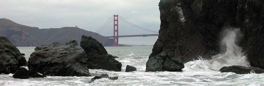 Golden Gate Bridge with rocks and waves - detail