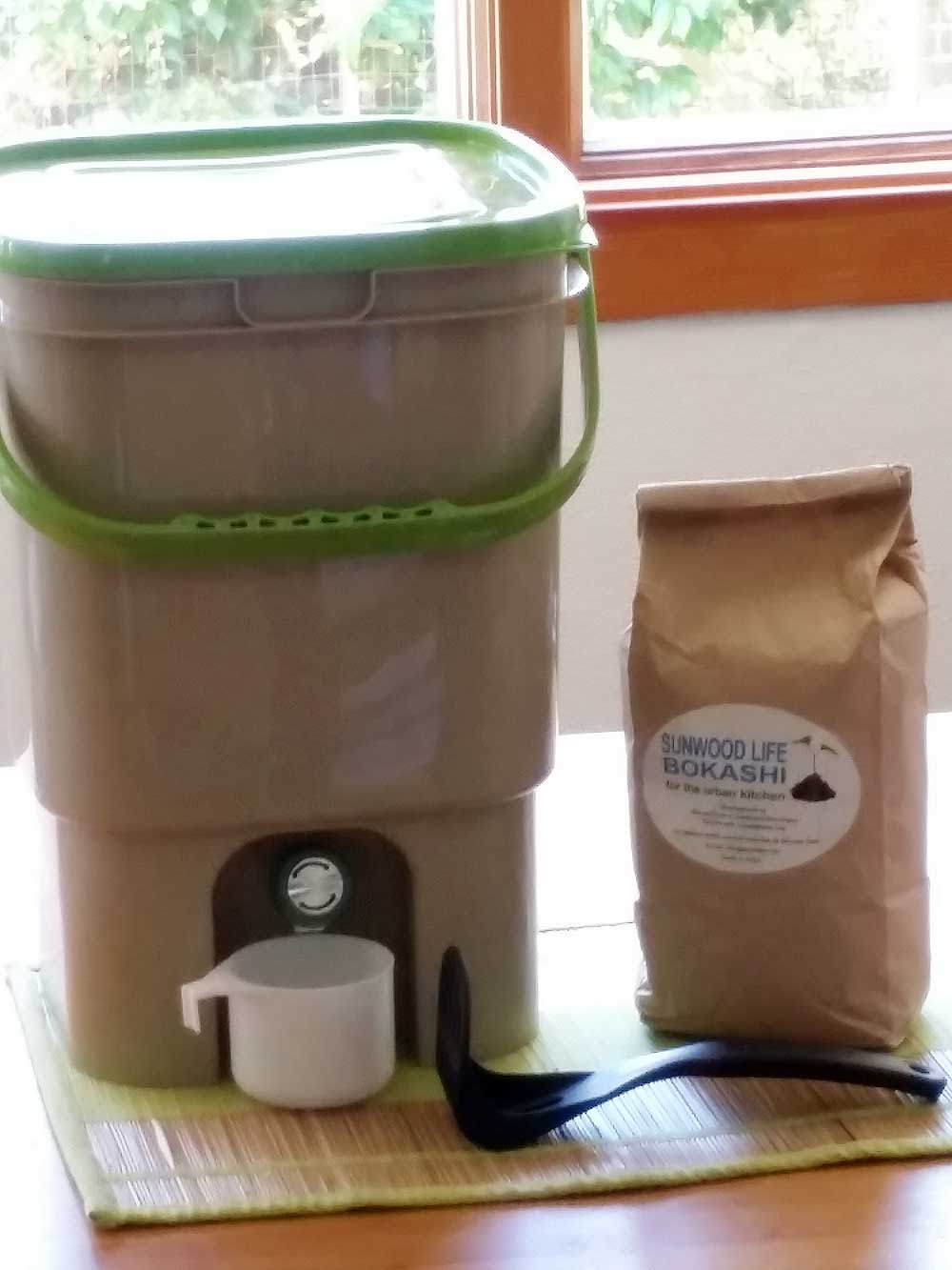 Bokashi system: pail with tight lid and spigot, cup for Bokashi tea, implement for pressing down food waste materials, and Bokashi starter.