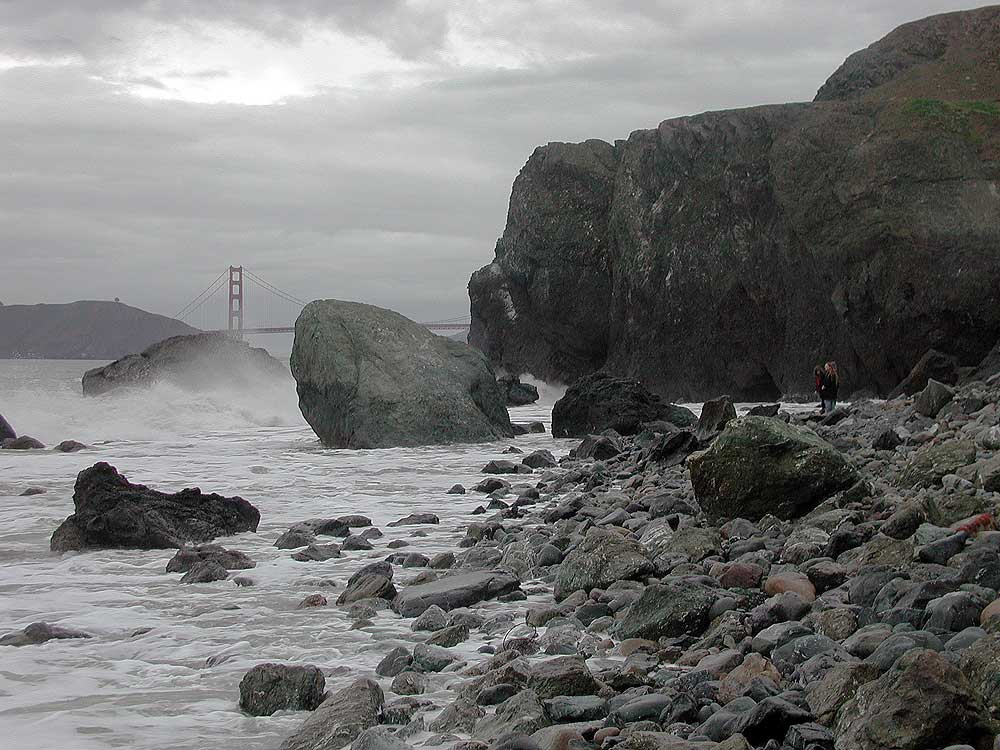 Golden Gate Bridge with rocks and waves.
